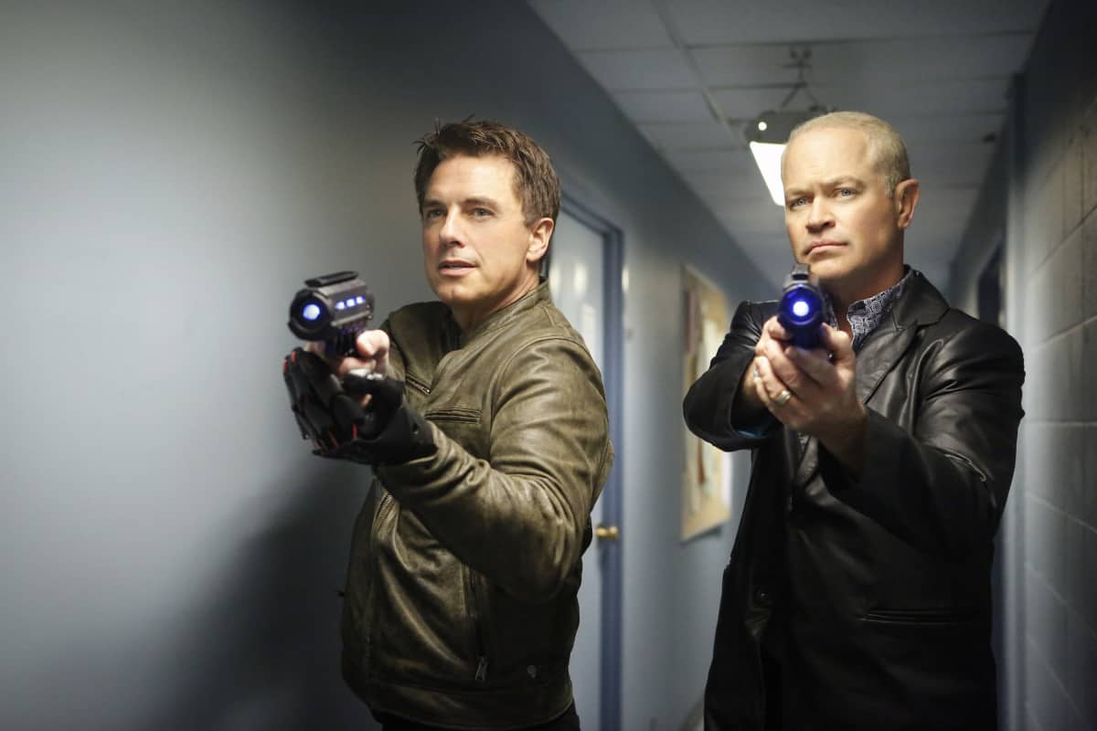 """DC's Legends of Tomorrow --""""Raiders of the Lost Art""""-- LGN209b_0135.jpg -- Pictured (L-R): John Barrowman as Malcolm Merlyn and Neal McDonough as Damien Darhk -- Photo: Bettina Strauss/The CW -- © 2017 The CW Network, LLC. All Rights Reserved"""